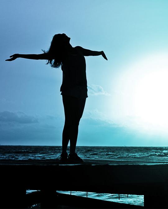 femme bras tendus vers le ciel